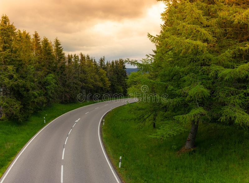 An empty winding road at sunset in the Black Forest in Germany. Street, alpine, asphalt, beautiful, clouds, colorful, concrete, curve, curved, deserted royalty free stock image
