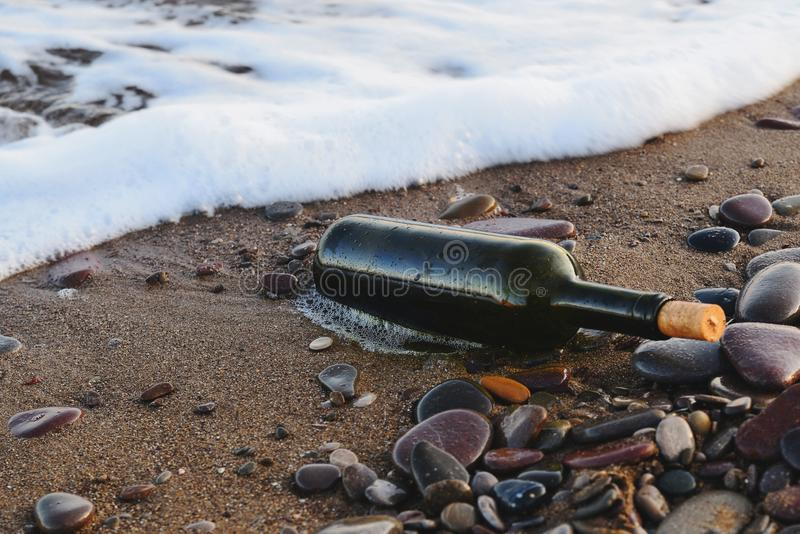 Empty green wine bottle wave thrown on the beach. Empty wine bottle plugged with a cork stopper lying on a sandy beach stock images