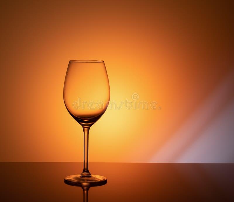 Empty glass goblet on orange background royalty free stock photos