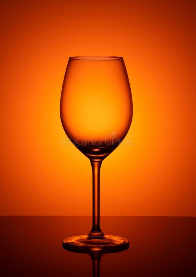 Empty glass goblet on orange background royalty free stock image