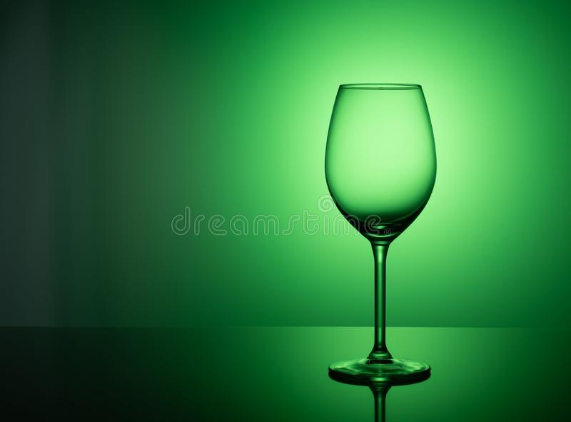 Empty glass stands on acrylic glass on a green background. An empty wine glass stands on an acrylic glass on a green background. green Background Concept Purity royalty free stock photo