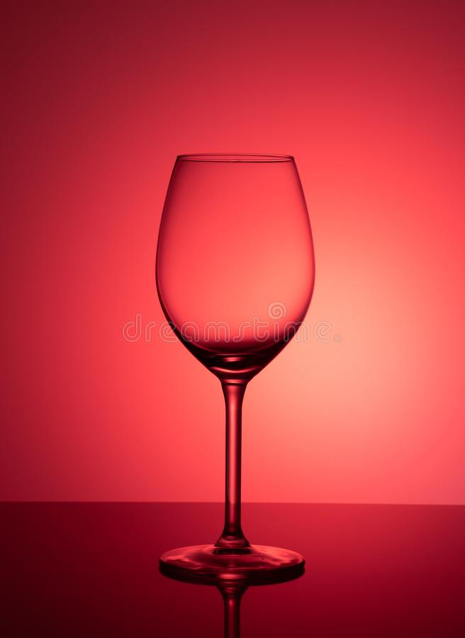 Empty glass stands on acrylic glass on a pink background royalty free stock photos