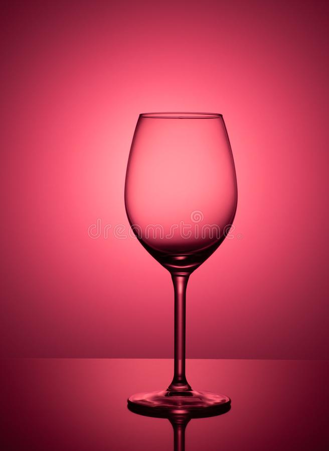Empty glass stands on acrylic glass on a pink background stock photography