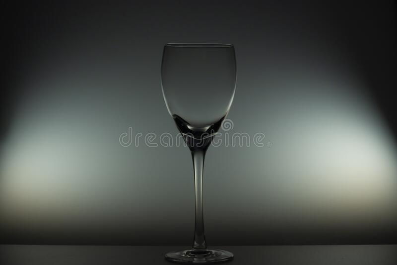 Empty wine glass stands on the table. In the dark royalty free stock photo