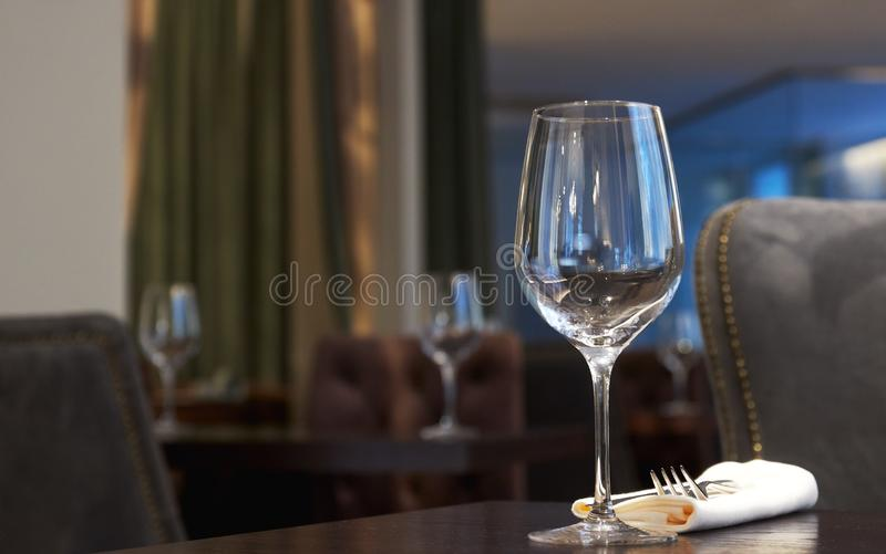 Empty wine glass on a table in a restaurant. background is out of focus. interior in a restaurant royalty free stock photo