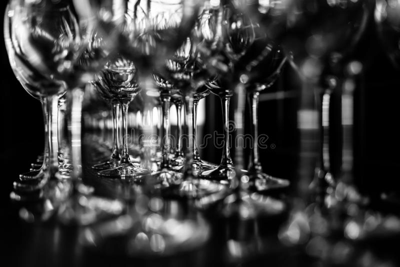Empty wine glasses. Beautiful new glasses for wine from glass stand in even rows on a wooden table in a restaurant royalty free stock photos