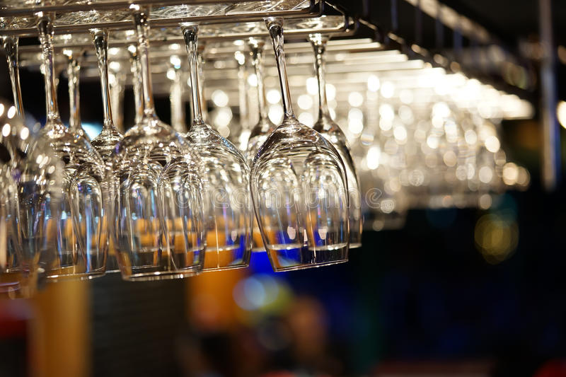 Empty wine glasses hanging on bar rack with bokeh background. Modern restaurant, kitchen utensils, or romantic dinner concept.  royalty free stock photos