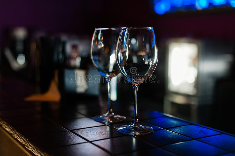 Empty wine glasses in row on bar or restaurant. Empty wine glasses in row on bar with bokeh. Dark background royalty free stock photo