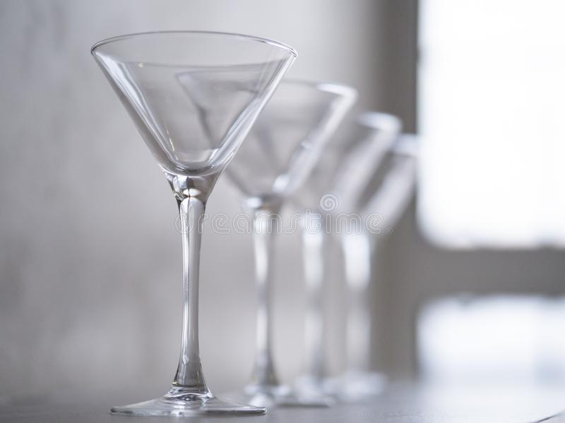 Empty wine glasses on a window sill, sea and sky in the blurred background royalty free stock images