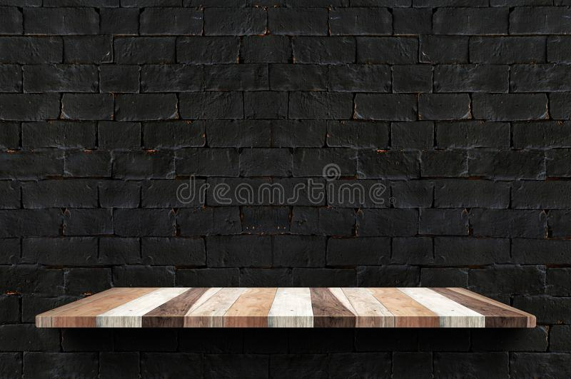 Empty wood board shelf at black brick wall background,Mock up for display or montage of product or design.  royalty free stock image