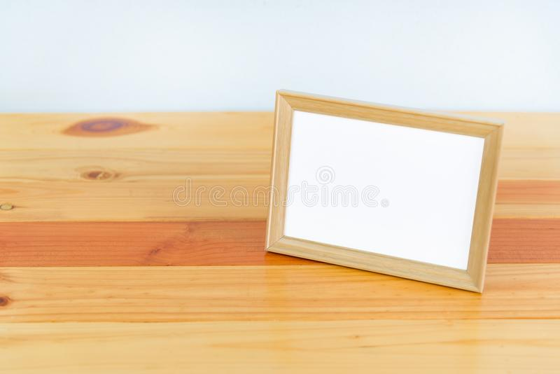 Empty wood photo frame on wooden table with copy space, picture stock image