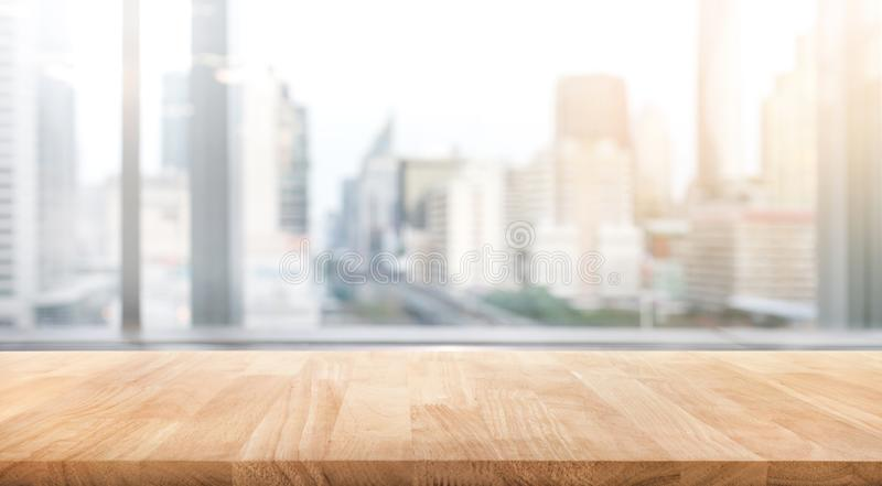 Empty wood table with blur room office and window city view stock image