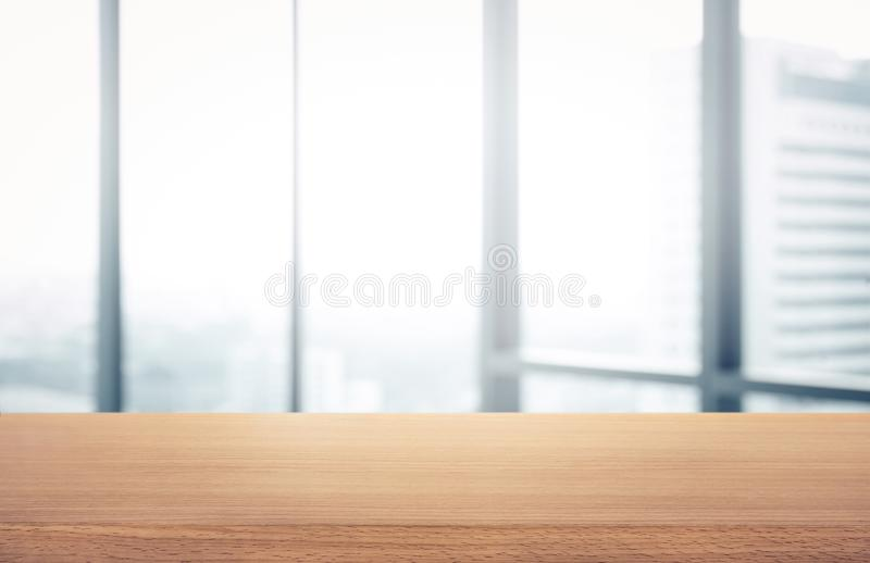 Empty wood table with blur room office and window city view royalty free stock image