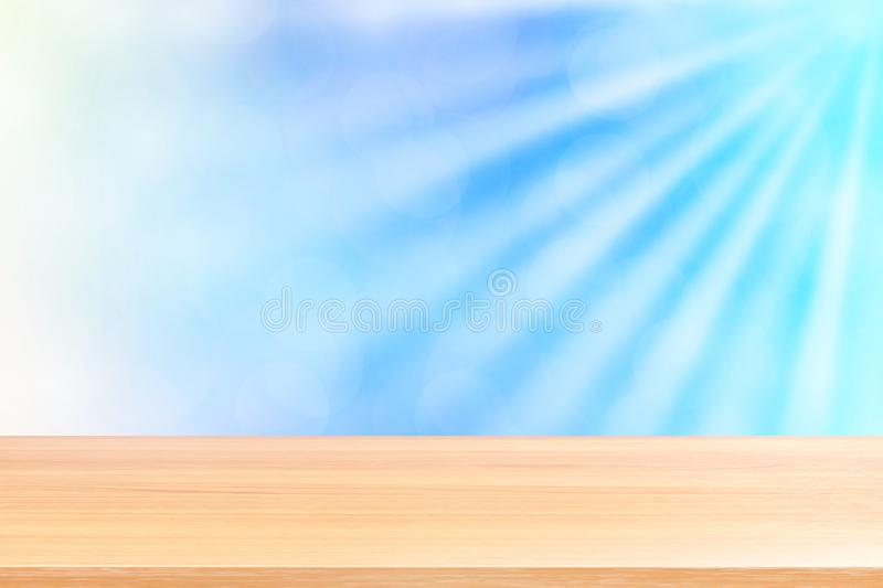 Empty wood table floors on soft blue bokeh lights beam shine gradient background, wooden plank empty on blue bokeh colorful light. The empty wood table floors on stock images