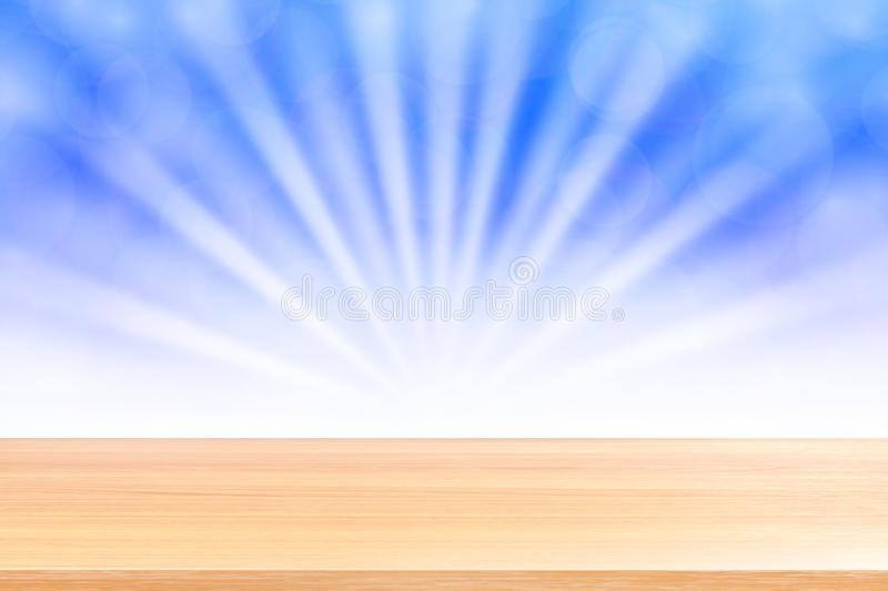 Empty wood table floors on soft blue bokeh lights beam shine gradient background, wooden plank empty on blue bokeh colorful light. The empty wood table floors on stock photography