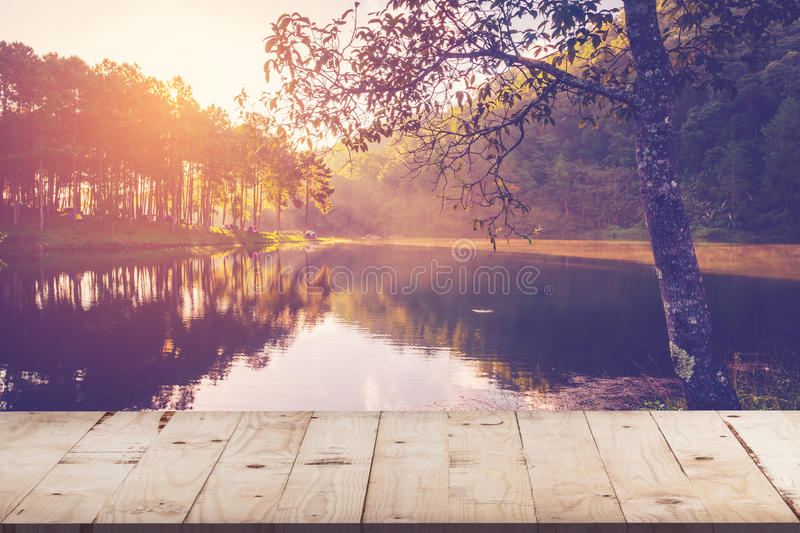 Empty wood table for product display and montage on pond water a stock photos