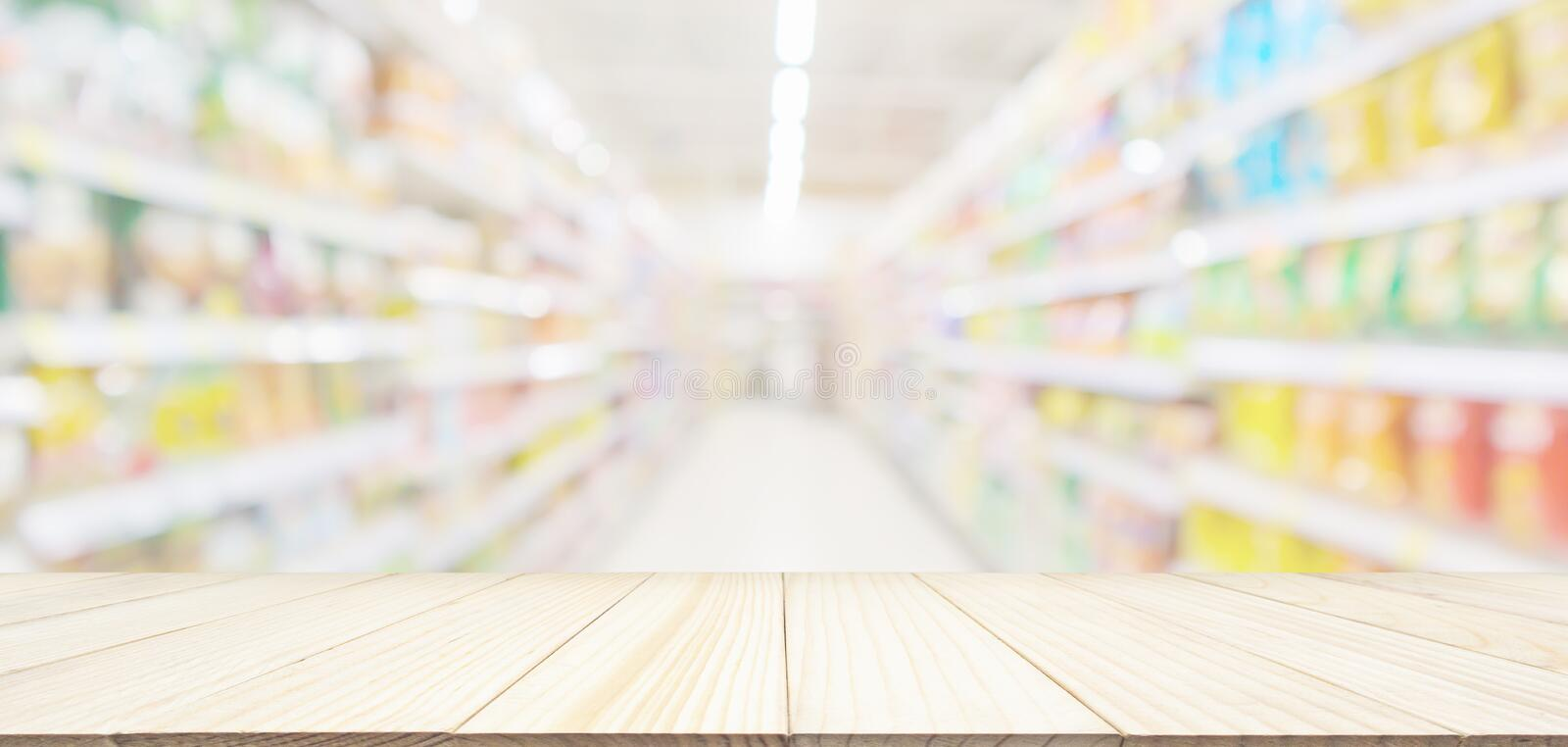 Empty wood table top with abstract supermarket aisle interior blurred defocused background. Empty wood table top with abstract supermarket grocery store aisle royalty free stock photo