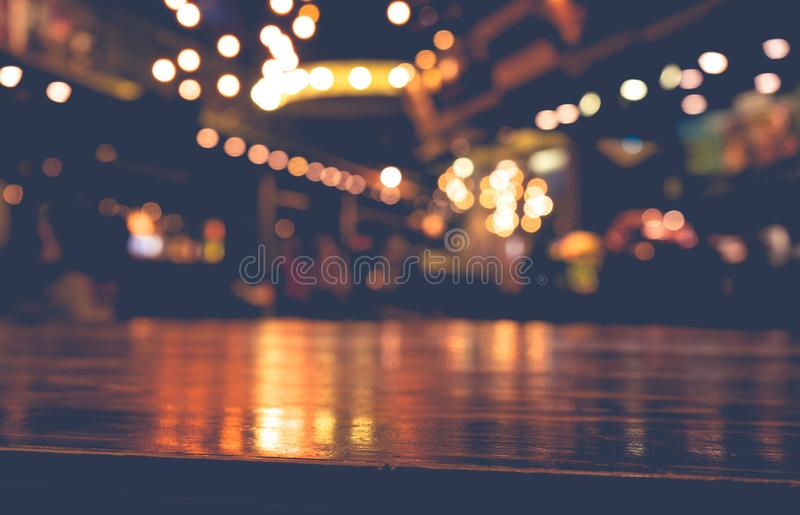 Empty wood table top bar on blur cafe restaurant in dark background stock photography