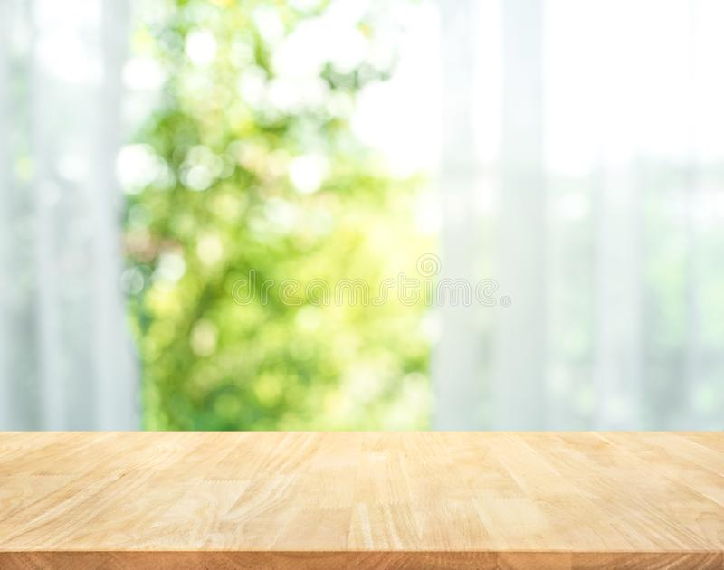 Empty of wood table top on blur of curtain with window view royalty free stock photography