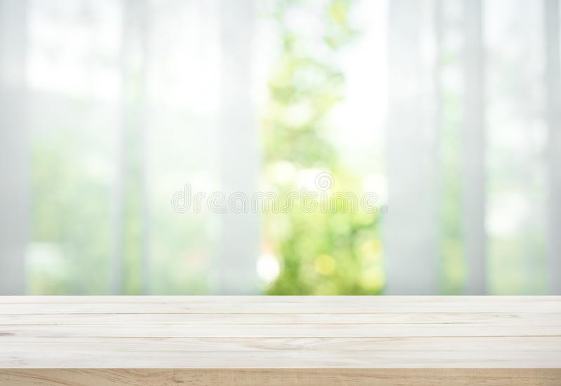Empty of wood table top on blur of curtain with window view green from tree garden. Background.For montage product display or design key visual layout royalty free stock photography