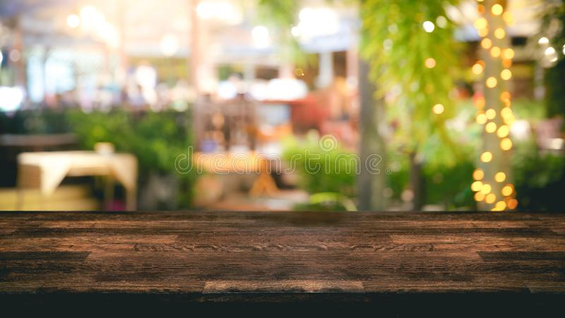 Empty wood table top and Blur light reflection on scene at restaurant, pub or bar at night. Empty wood table top and Blur light reflection green palm leaves or royalty free stock photo