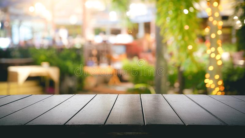 Empty wood table top and Blur light reflection on scene at restaurant, pub or bar at night stock photography