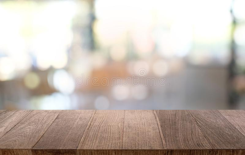 Empty wood table top and blur of night market background/selective focus .For montage product display. Empty wood table top and blur of night market background/ stock photography