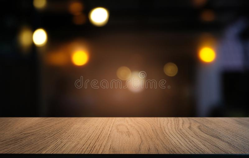 Empty wood table top and blur of night market background/selective focus .For montage product display. Empty wood table top and blur of night market background/ royalty free stock photography