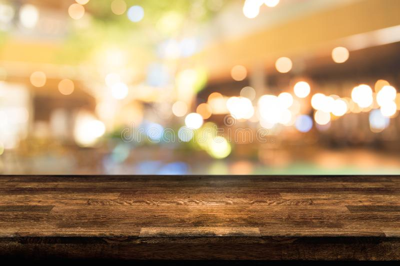 Empty wood table top and blur of night pub or restaurant background/selective royalty free stock photo