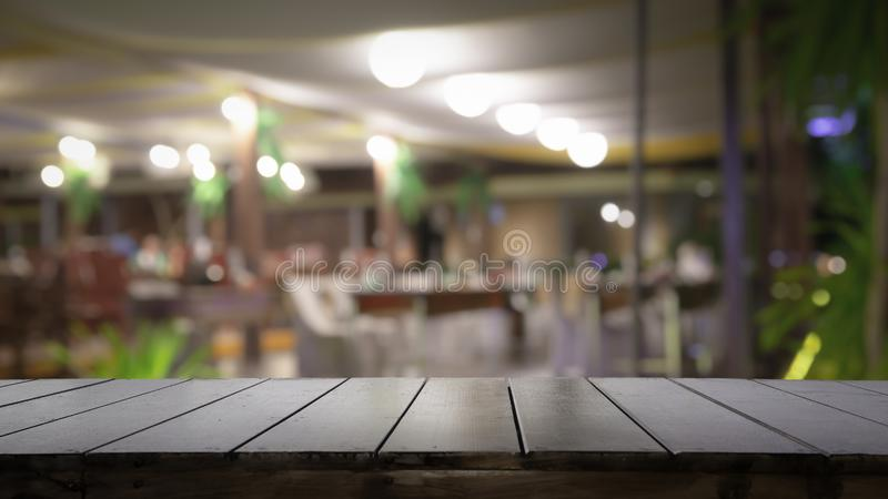 Empty wood table top and blur of night pub or restaurant background selective focus stock image
