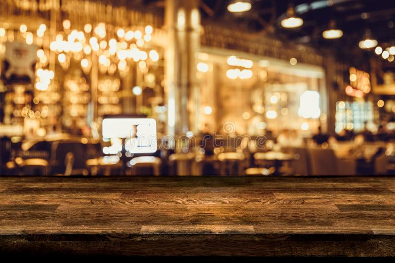 Empty wood table top and blur of night pub or restaurant stock images