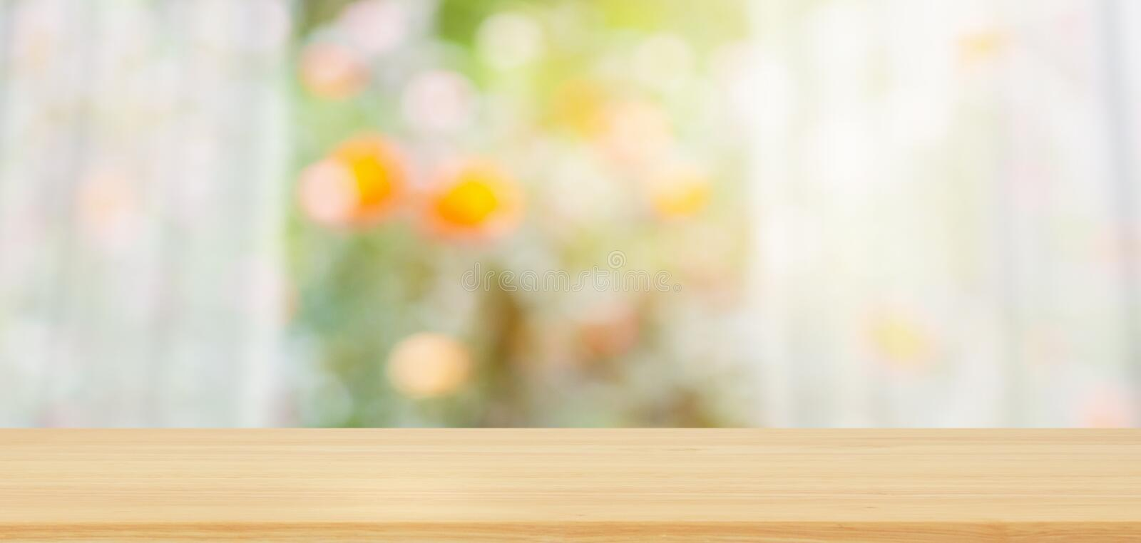 Empty wood table top with blur white curtain window and green garden background royalty free stock photography