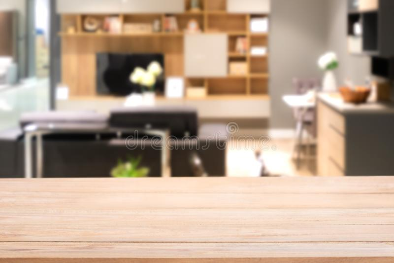 Empty wood table top with Blurred abstract mock up of modern living room interior. With elegant black leather sofa. Decorated with shelf, TV and dining table stock image