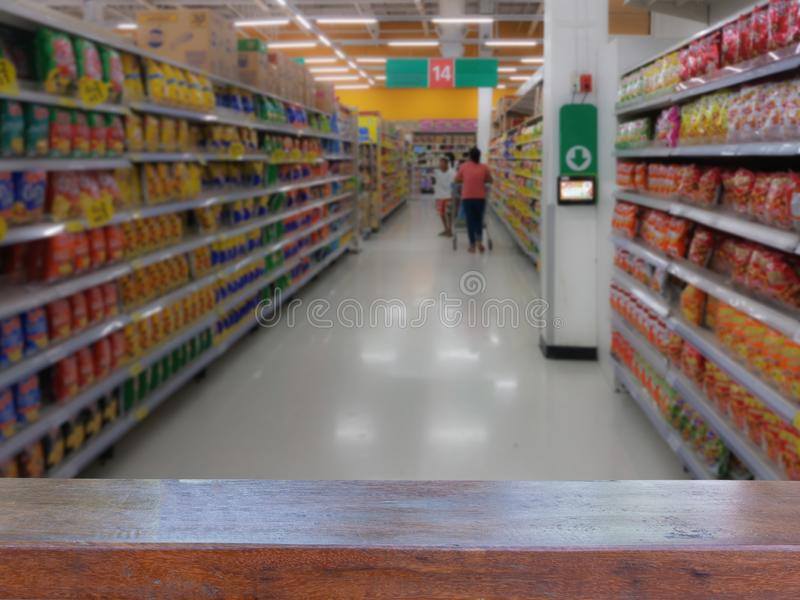 Empty wood table top on Blurred people shopping in selection of Snack on shelf in supermarket or department store, products on royalty free stock photography
