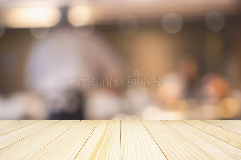Empty wood table top with Chef cooking in restaurant kitchen abstract blurred background stock photography