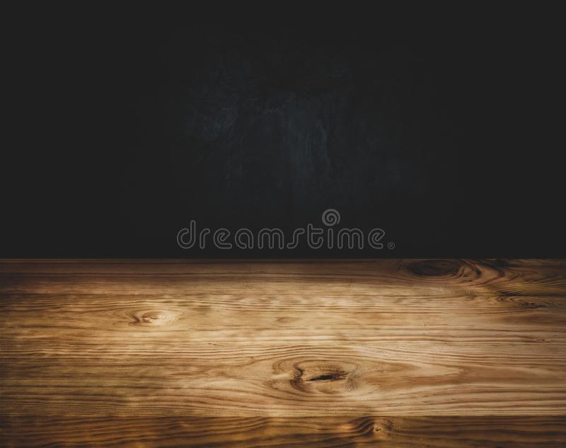 Empty wood table top counter on dark wall background stock photos
