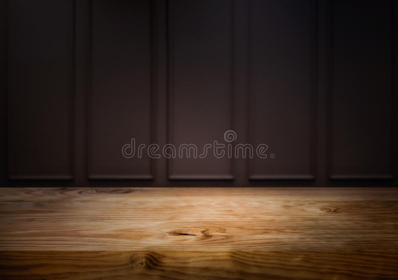 Empty wood table top counter on dark yellow wall background.For create product display or design key visual stock photos
