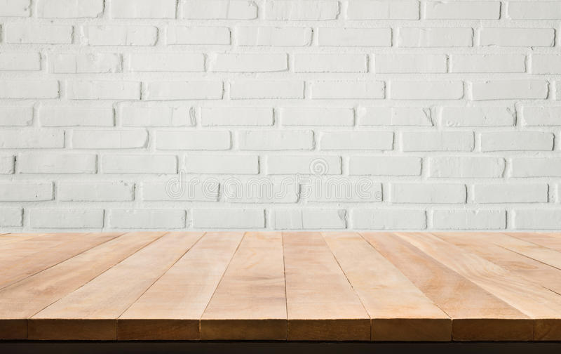 Empty wood table top with white brick wall background. stock image