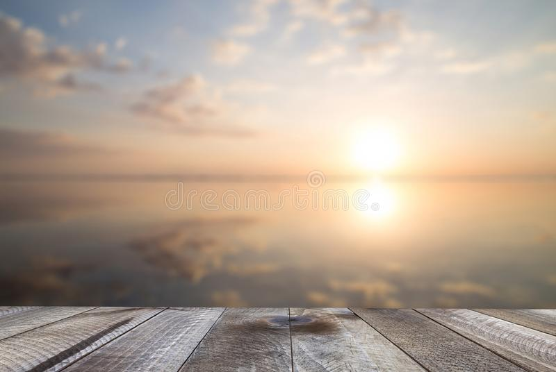 Empty woodeen table top and beautiful ocean at sunset. Summer background.  stock photos