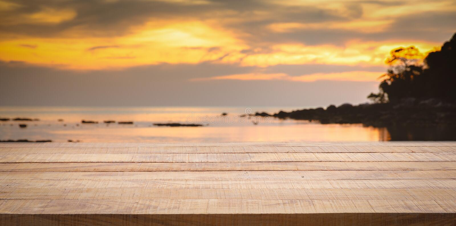 Empty wooden bar counter with blurred sunset beach background. Using for Mock up template for craft display of your design,Banner for advertise of product stock photography