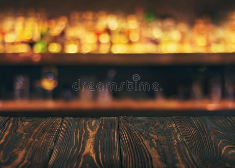 Empty wooden bar table top with defocused background. Bar counter table in front of blurred beaverages and drinks royalty free stock image