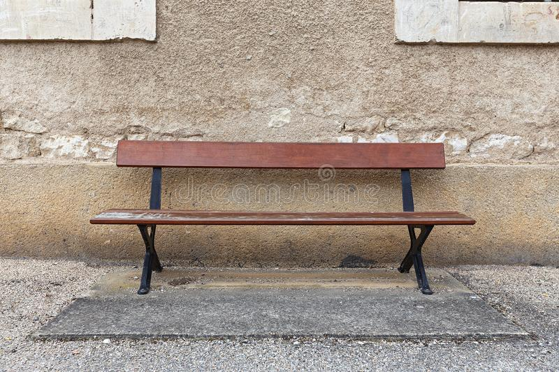 An empty bench against the wall royalty free stock photo