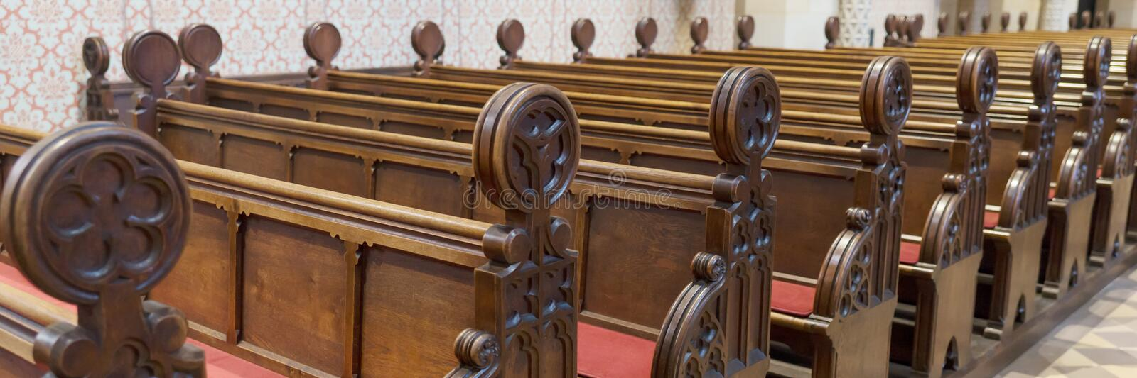 Empty wooden bench rows in the church. Empty wooden bench rows in the Catholic church stock image
