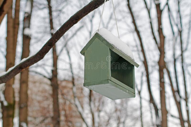 Empty wooden bird feeder hanging on a tree. In the winter park stock photography