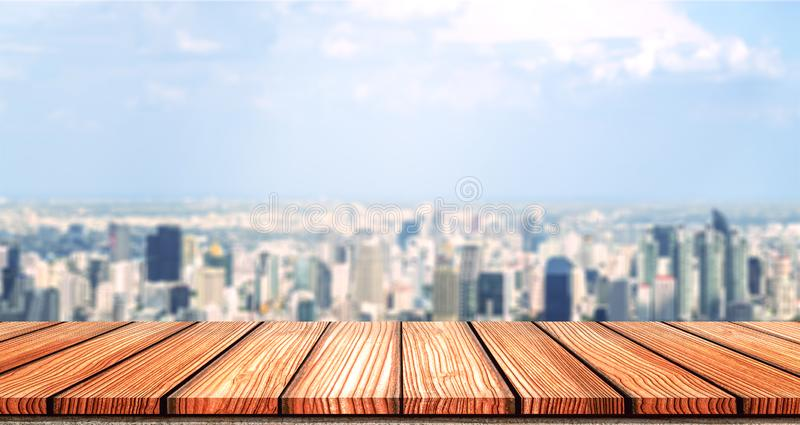 Empty Wooden board top table in front of city blurred background. Perspective wood in blurred city scape background for photo. Montage, product display or mock stock images