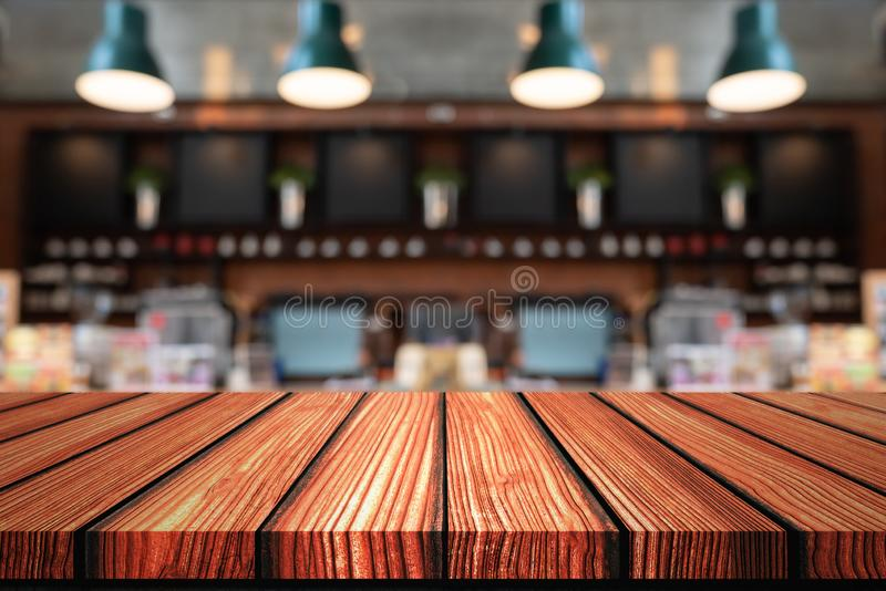 Empty Wooden board top table in front of counter coffee shop blurred background. Perspective wood in blurred coffee cafe royalty free stock image