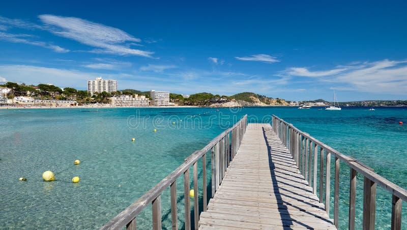 Empty wooden boardwalk leading to Mediterranean Sea stock photo
