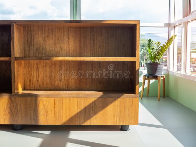 Empty wooden book shelf. Near window glass with light and shadow on sunny day in cafe royalty free stock image