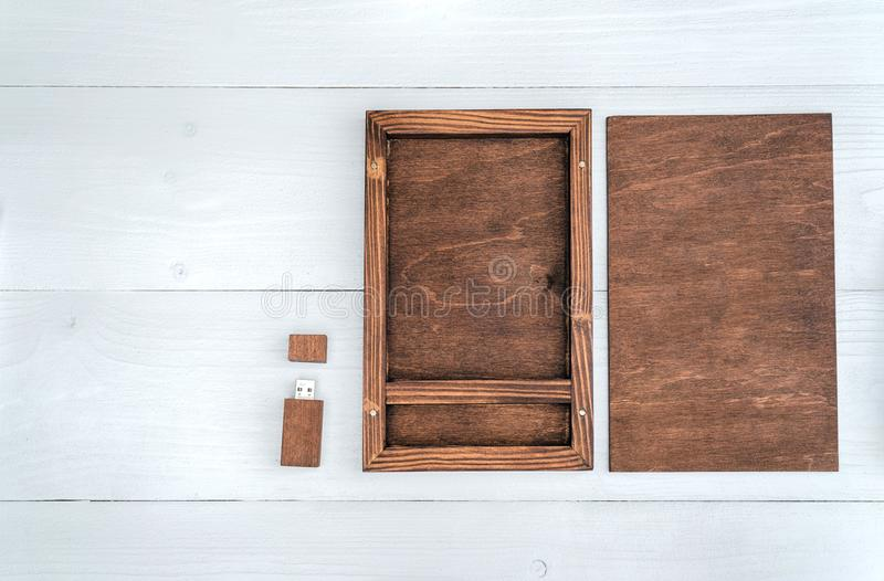 Empty wooden box for gift or photo with usb stick, free space. Ackaging for photo and USB drives on white wooden background. Information and mail concept stock photos