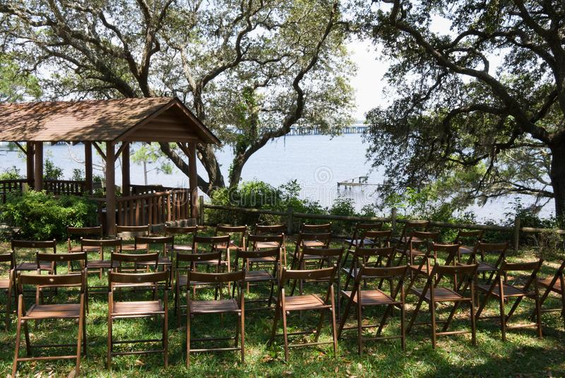 Empty Wooden Chairs and a Rustic Outdoor Gazebo Waters Edge. Rows of empty brown colored wooden chairs in front of a rustic outdoor covered gazebo . All under royalty free stock image